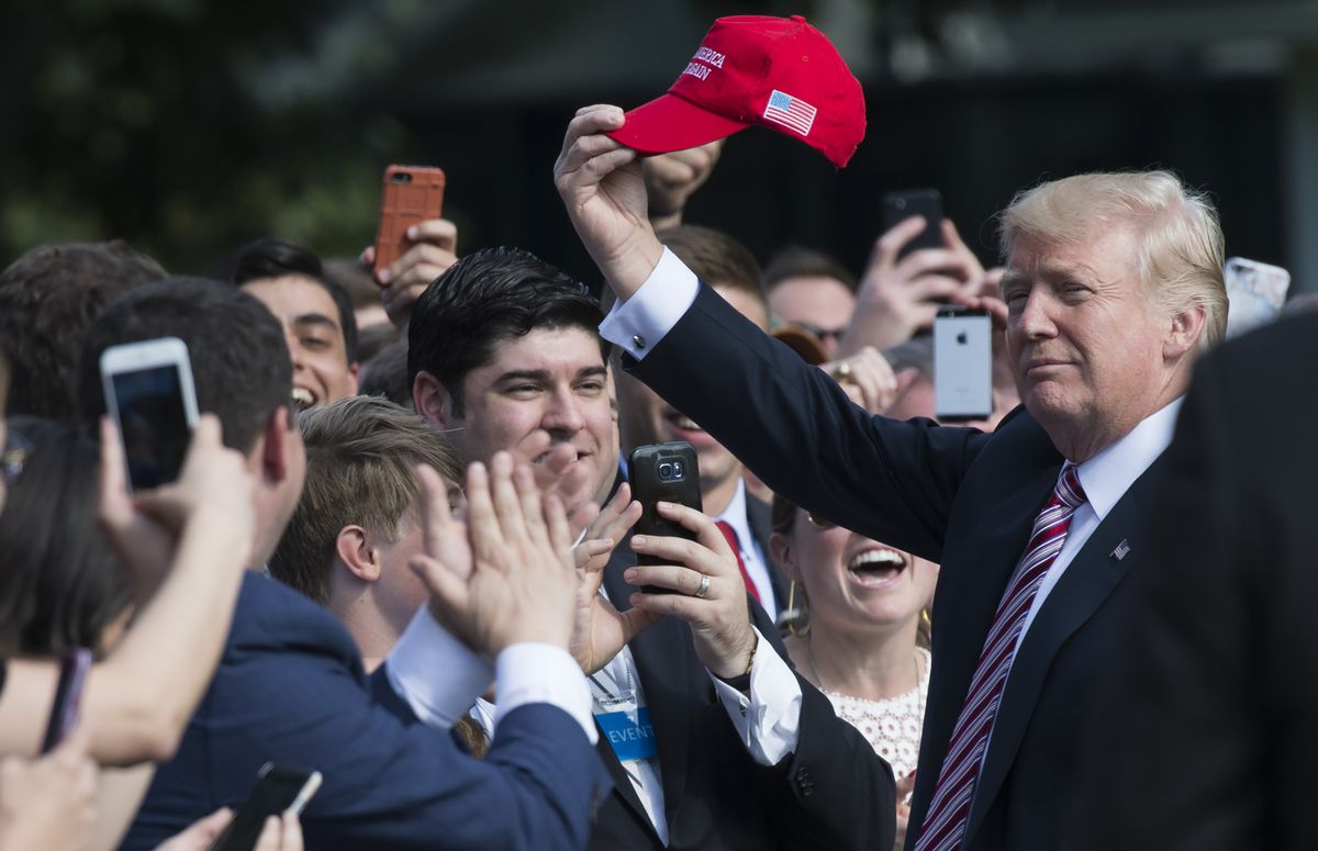 """Donald Trump waves a """"Make America Great Again"""" hat before a group of supporters."""