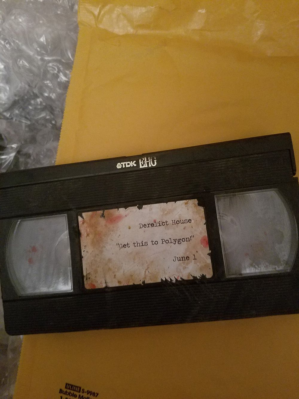 """This image shows a beaten up and bloody videocassette. Written on the front of the cassette are the lines: """"Derelict House, Get this to Polygon! June 1."""" Below the cassette are a padded envelope and box which have been opened."""