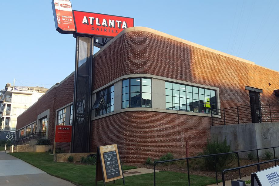 A brick building with Atlanta Dairies sign over the top of it.