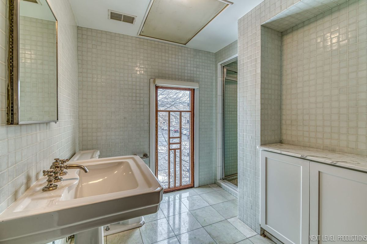 A tiled bathroom with a pedestal sink and a narrow vertical window with wood casings.