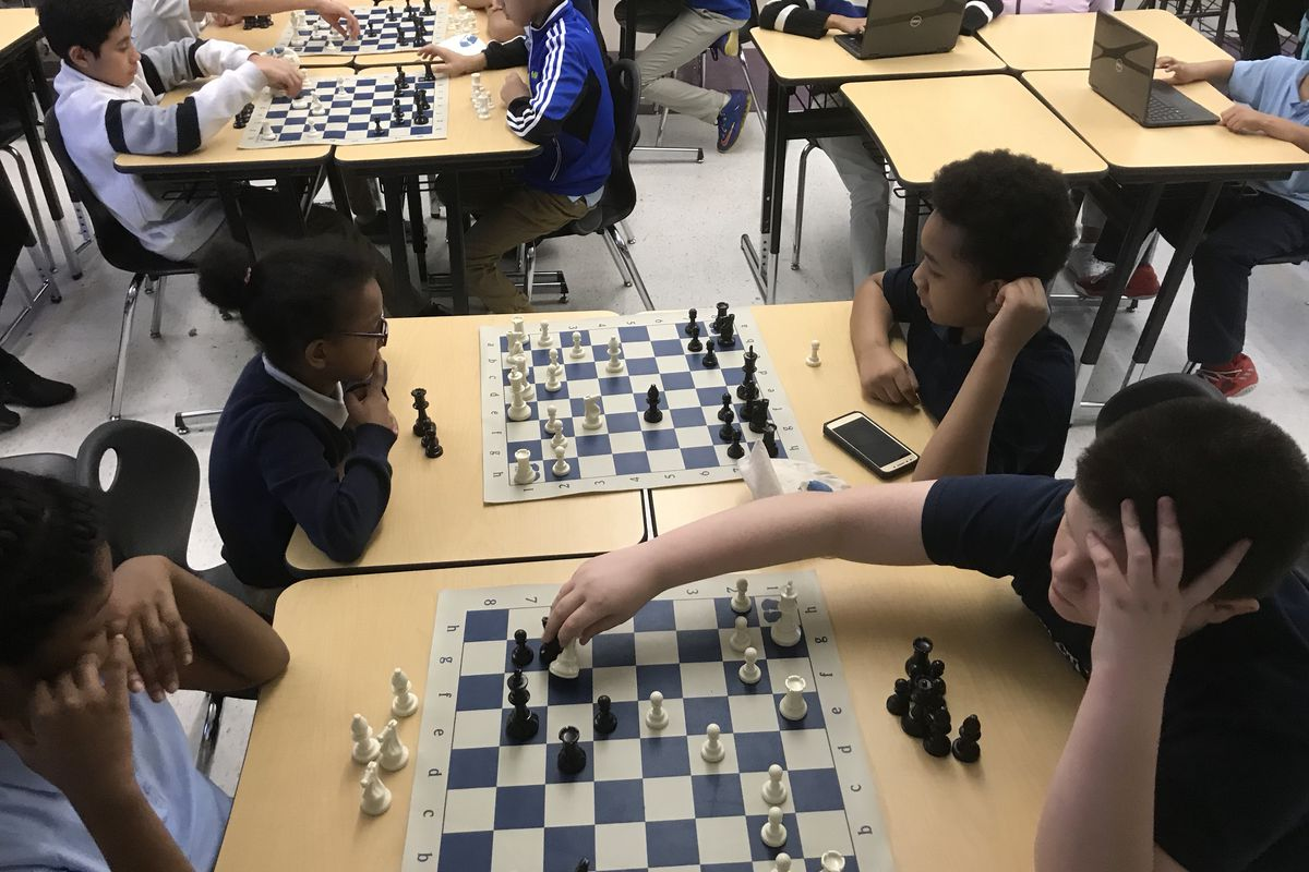 Mia Singleton, left, and Shaun Tinker, both in foreground, engage in a chess game during practice Tuesday at Munger Elementary-Middle School in Detroit