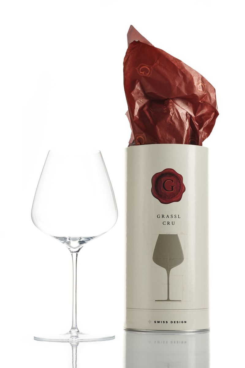 An empty wine glass next to a cylindrical wine glass packaging with red tissue paper at the top