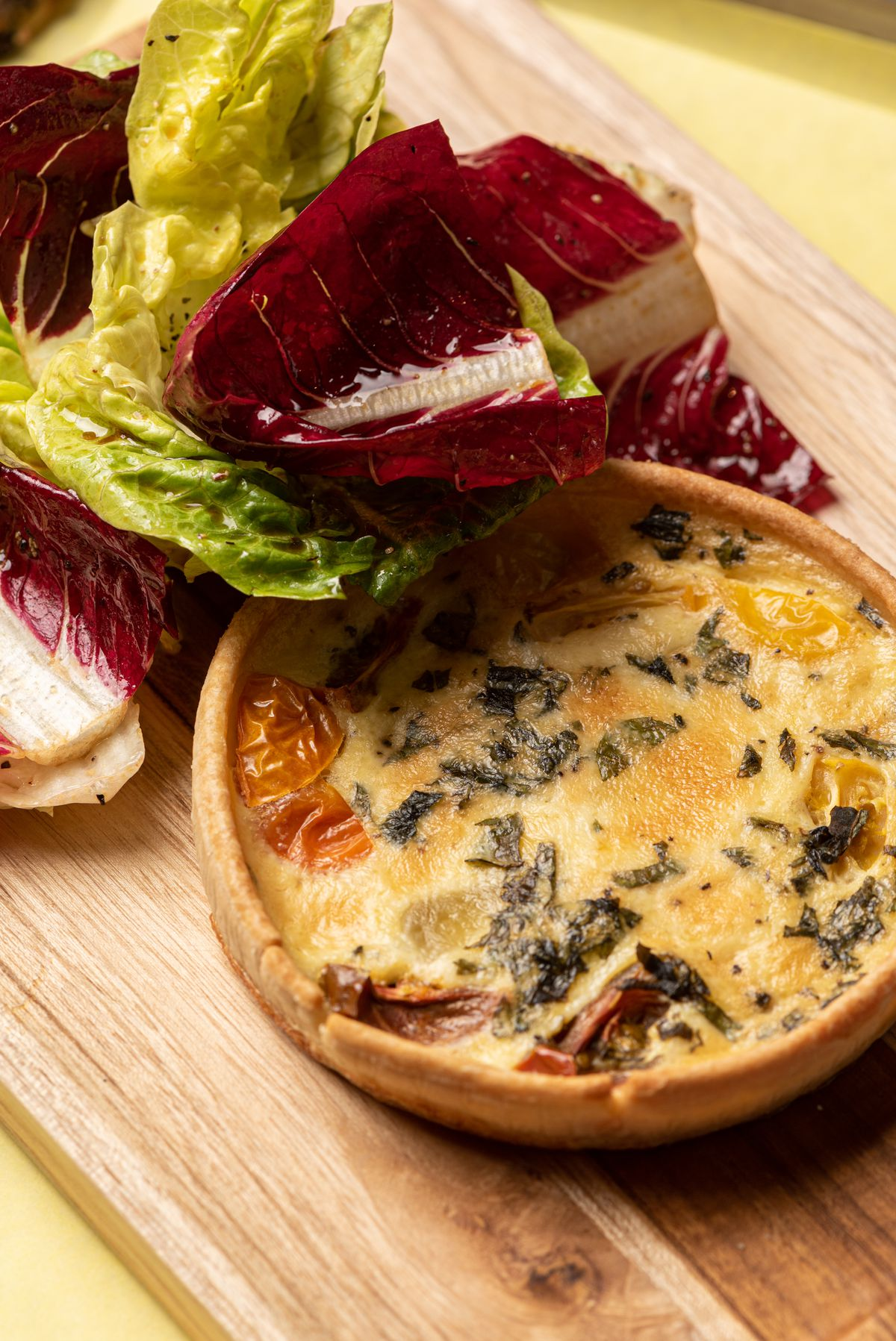 An overhead shot of a single-serving round quiche with side salad.