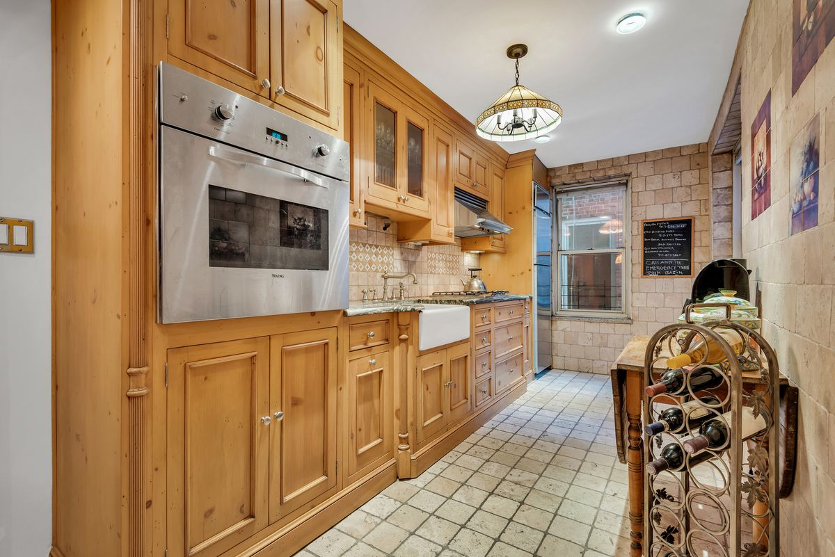 A kitchen with wood cabinetry and beige tiles on its walls.