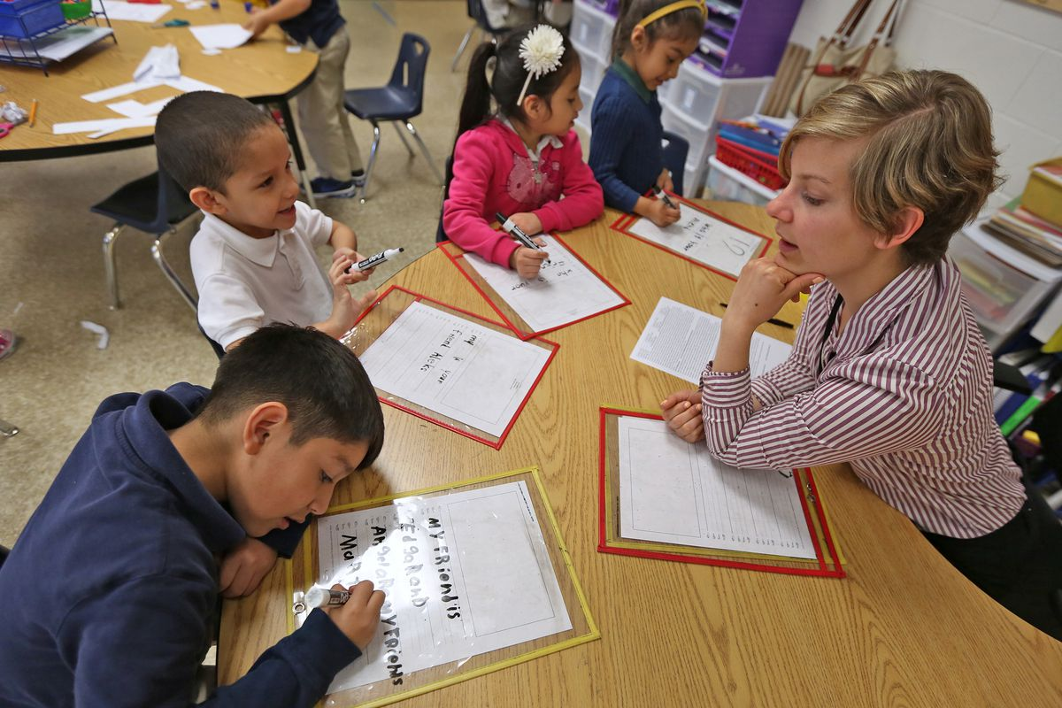 Lead Kindergarten teacher Liz Amadio, right, works with students at Enlace Academy.