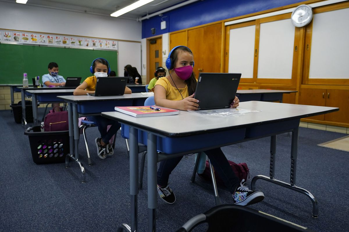 Masked students work on laptops at spaced out desks in a learning center.