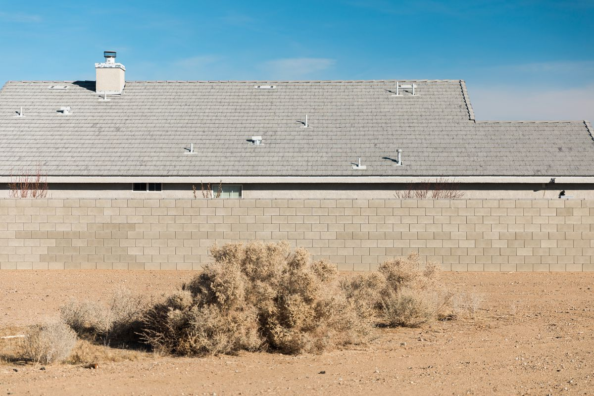 The exterior of a building in a desert. There is a tan brick fence in front of the building.