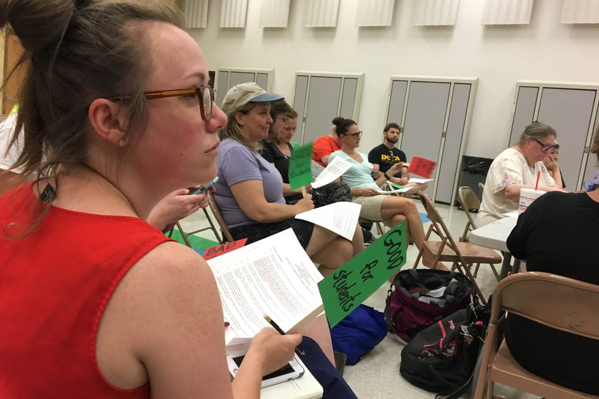 Teachers watch a master contract bargaining session between Denver Public Schools and the Denver teachers union on June 22.