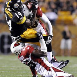 Pittsburgh Steelers wide receiver Limas Sweed (14) attempts a catch as Arizona Cardinals' Bryant McFadden (25) and linebacker Karlos Dansby (58) defend during the first quarter.