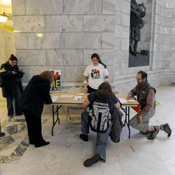 Kate Colbath, center, gets people to fill out postcards to be sent to their local representatives and Gov. Gary Herbert during the Utahns for the Medicaid Expansion rally in the rotunda at the state Capitol on Wednesday, Nov. 20, 2013, in Salt Lake City. The group rallied to show Herbert he has support if he decides to expand Medicaid.
