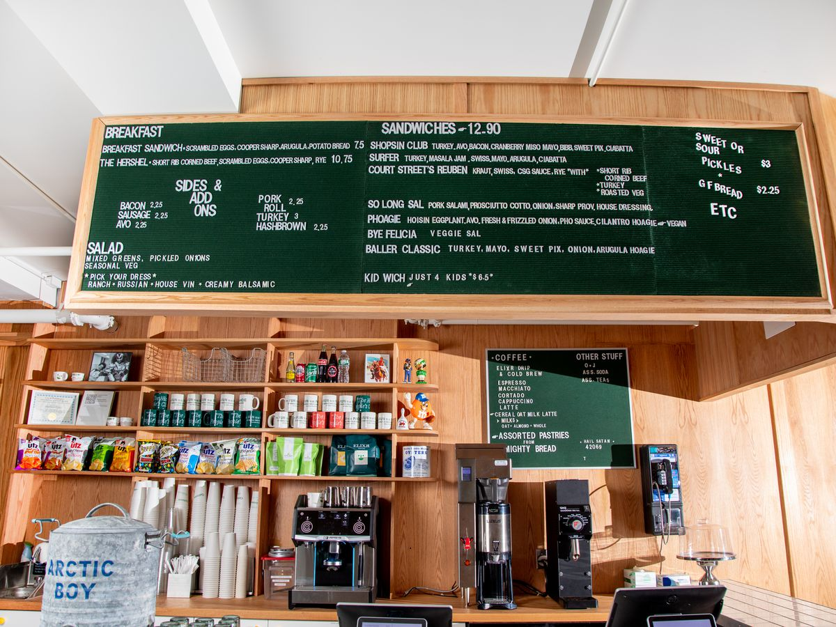 A coffee bar with blonde wood and a big peg board with sandwich menu items, then bags of chips, coffee mugs, and a percolator.