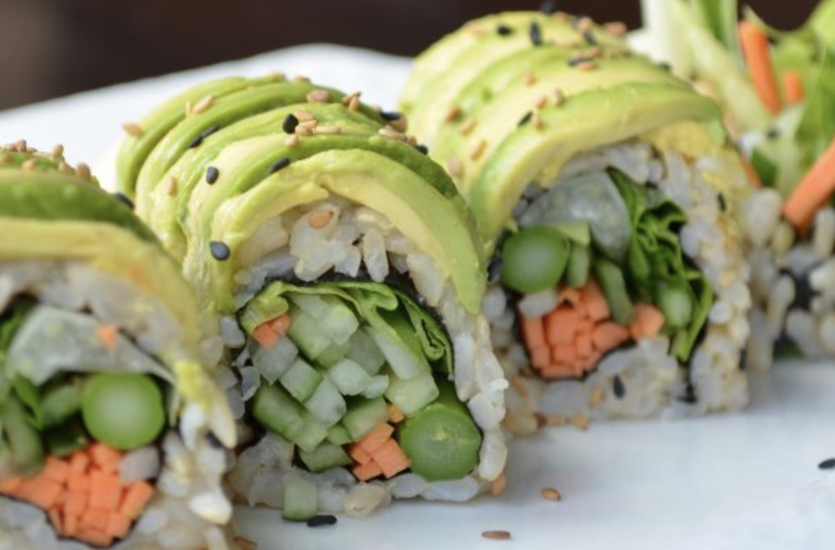 Four pieces of sushi, topped with avocado, sit atop a white plate