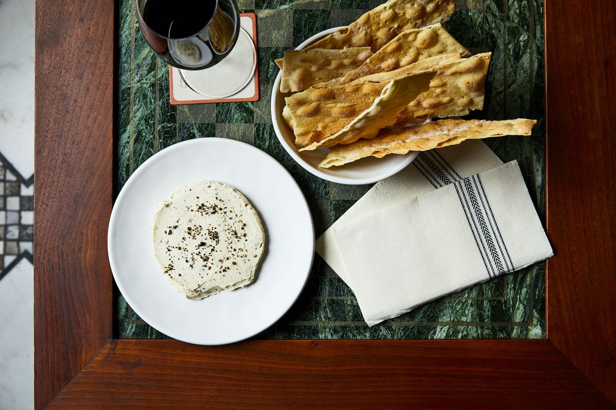 A white dip speckled with pepper is placed in a white plate on a green marble table. Also on the table are strips of rustic bread and a glass of red wine.