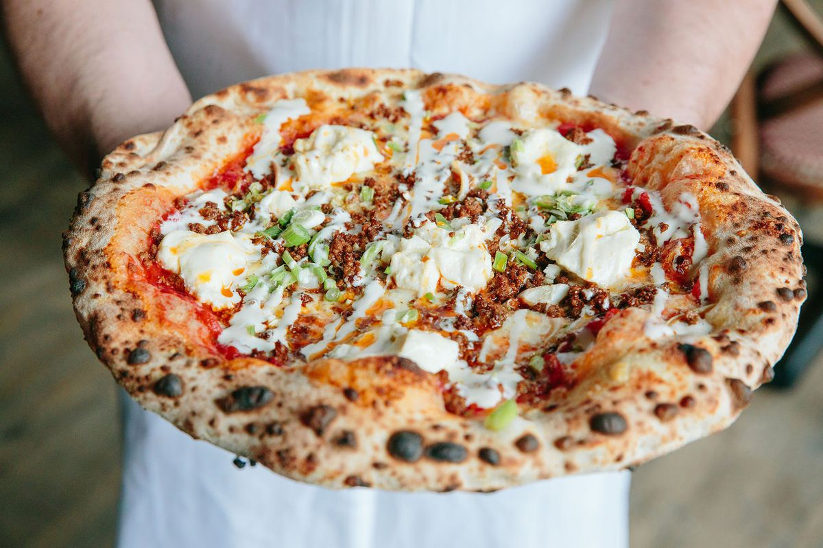 A chef holds a wood-fired pizza with a puffy, blistered crust at Posto in Somerville