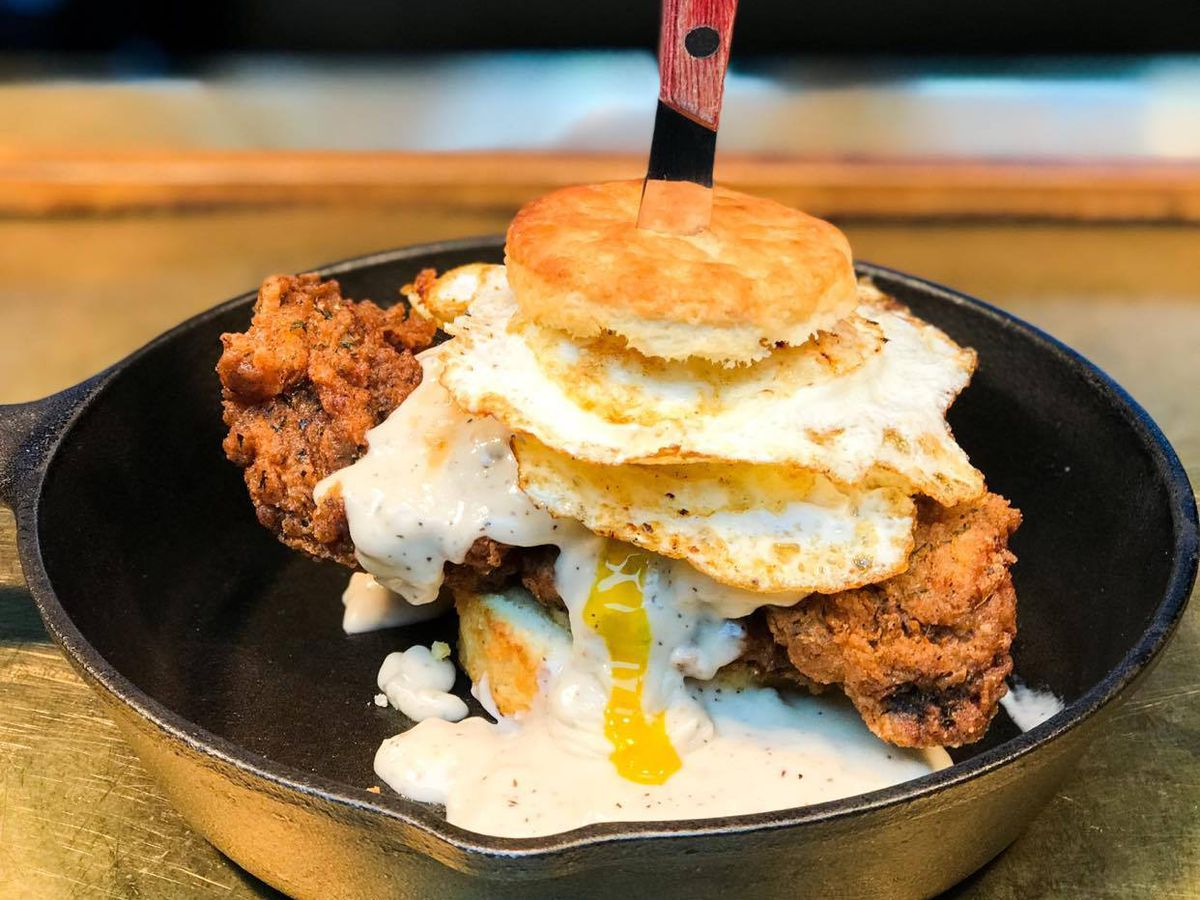 A fried steak sandwich in sliced biscuit with dripping eggs and gravy in a cast iron skillet