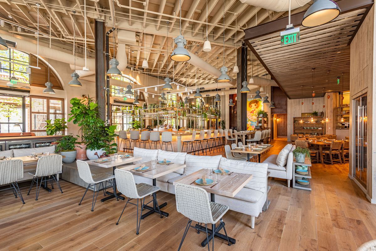 Tall ceilings in a new dining room of a restaurant with off-white seats.