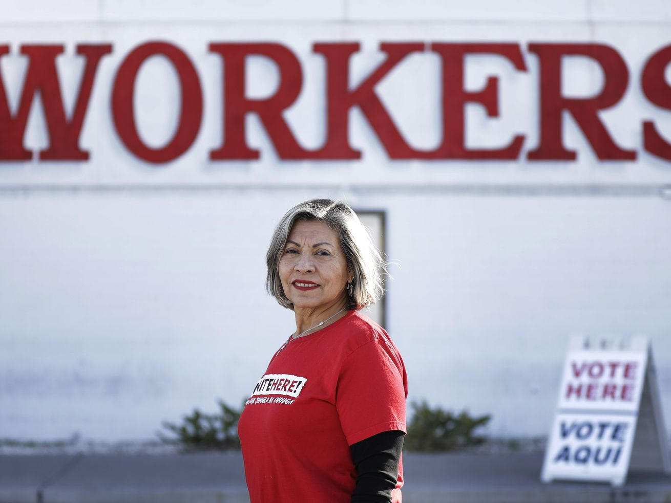 "A woman with gray hair and a red t-shirt reading ""Vote Here"" stands in front of a ""Workers"" sign."