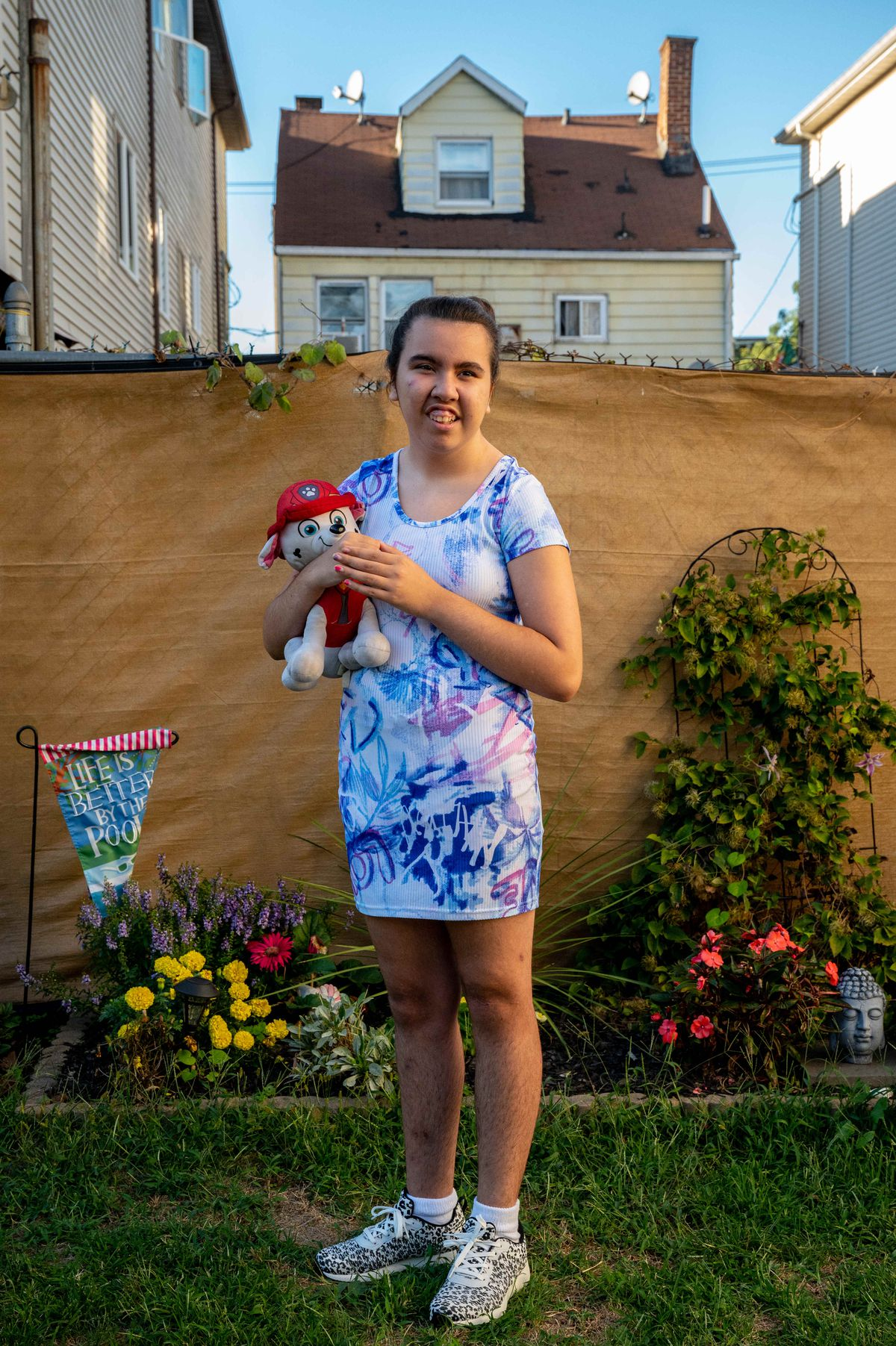A teenaged girl holding a stuffed animal poses for a portrait in her backyard.