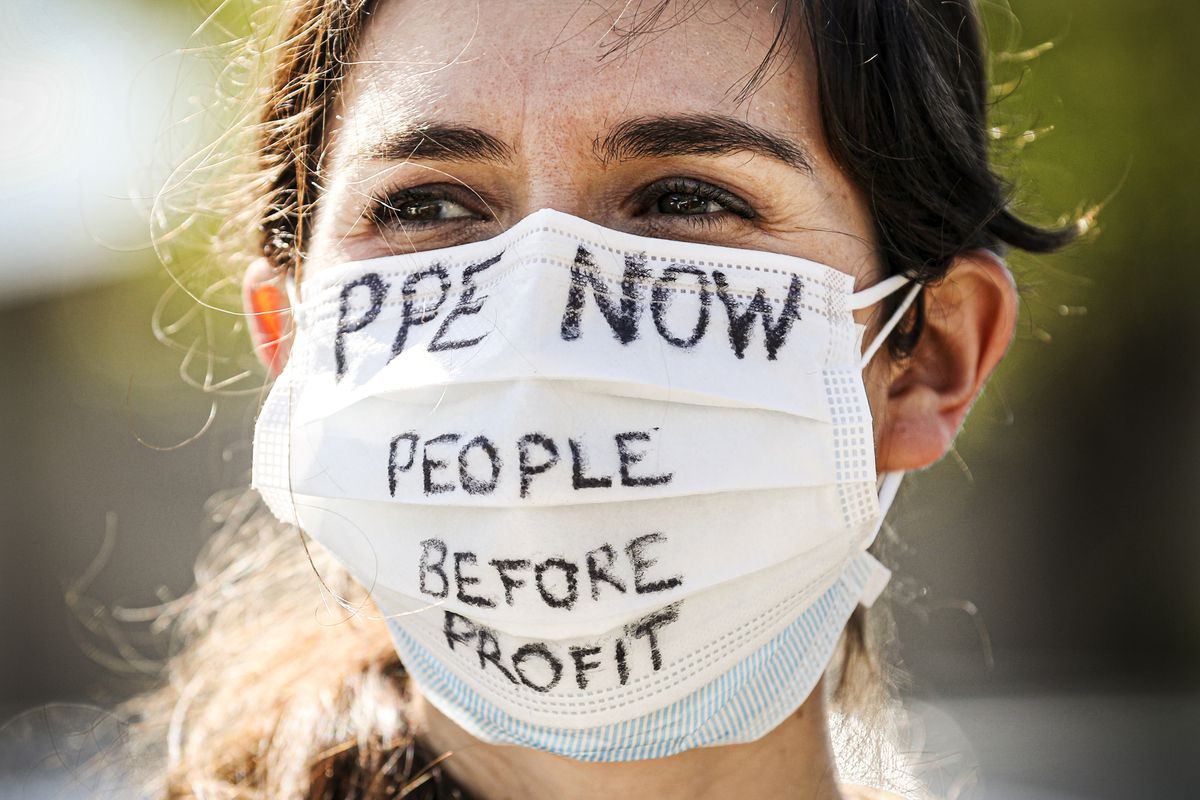 """A person in a breathing mask that reads """"PPE now, people before profit."""""""