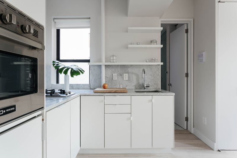 A kitchen with white cabinetry and a small window.