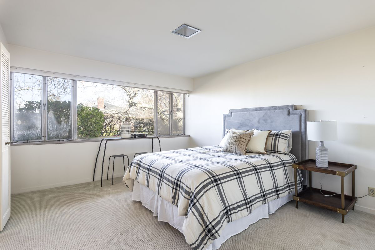 A plaid bed comforter sits on a bed in a white room.