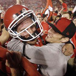 Utah fans storm the field and hug Utah Utes quarterback Jon Hays (9) after the Utes beat BYU in Salt Lake City  Sunday, Sept. 16, 2012. in Salt Lake City  Sunday, Sept. 16, 2012.