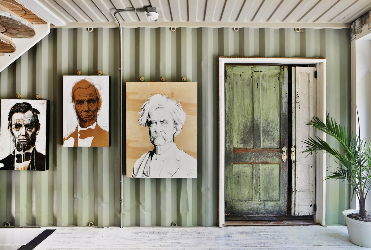 The couple who built the shipping container house left some metal walls exposed. Here, you see light-green metal walls and a white metal ceiling. Artwork by owner Zach Smithey, showing portraits of Abraham Lincoln and Mark Twain, decorates the walls.