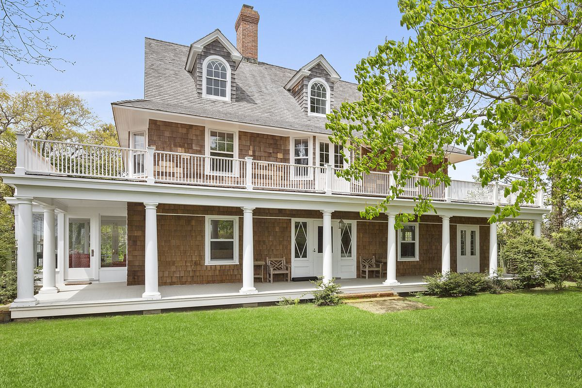 An exterior view of a shingled house called Wildmoor where Jackie Kennedy summered. The home has white trim and dormer windows. There is grass in front of the house.