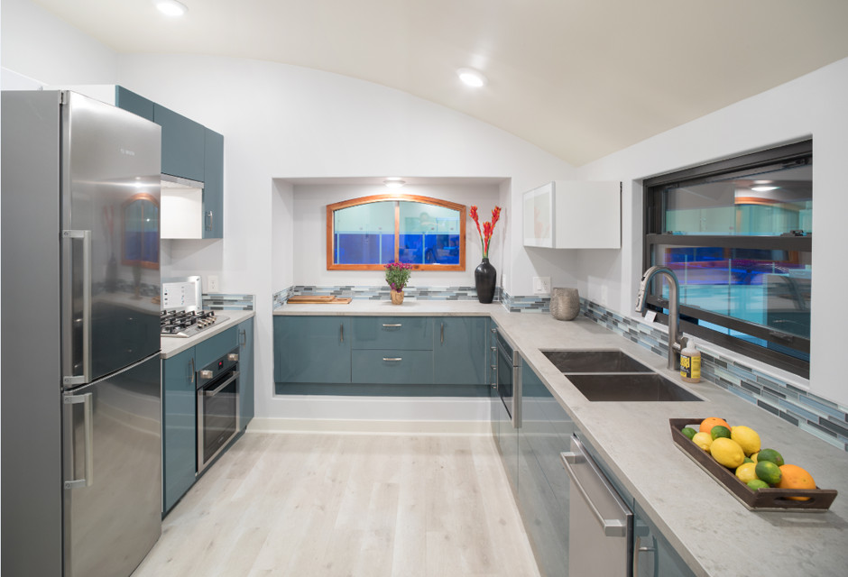 A kitchen area. The cabinetry is blue and there is a metallic silver refrigerator. There is a window over the sink.