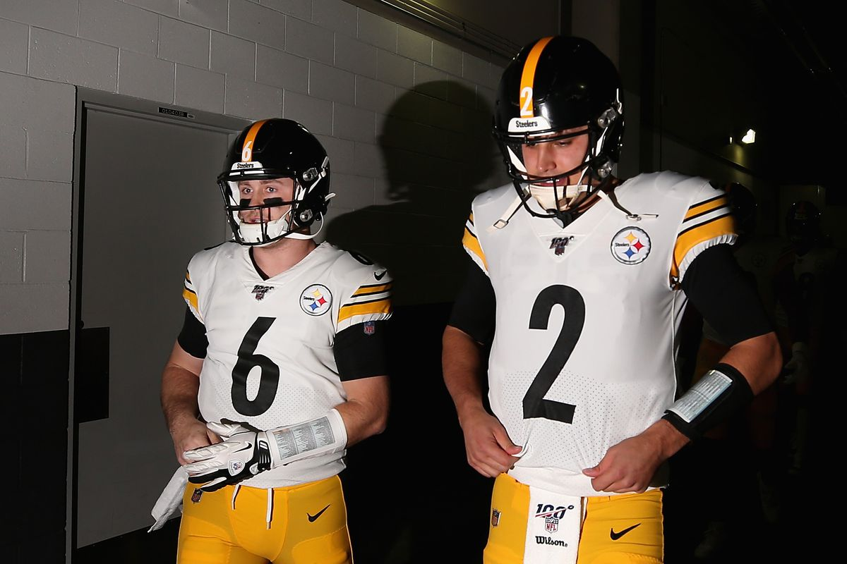 Quarterbacks Devlin Hodges and Mason Rudolph of the Pittsburgh Steelers walk out onto the field before the NFL game against the Arizona Cardinals at State Farm Stadium on December 08, 2019 in Glendale, Arizona.