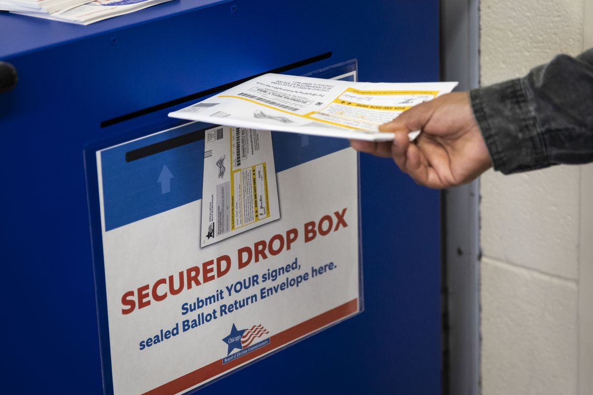 An early voter drops a mail-in ballot in the secured drop box at Warren Park in the West Rogers Park neighborhood on Wednesday.