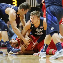 Brigham Young Cougars guard Kyle Collinsworth (5) and Brigham Young Cougars guard Jake Toolson (15) wrestle with Utah Utes forward Jordan Loveridge (21) for the ball as Utah and BYU play in the Huntsman Center in Salt Lake City Wednesday, Dec. 2, 2015.