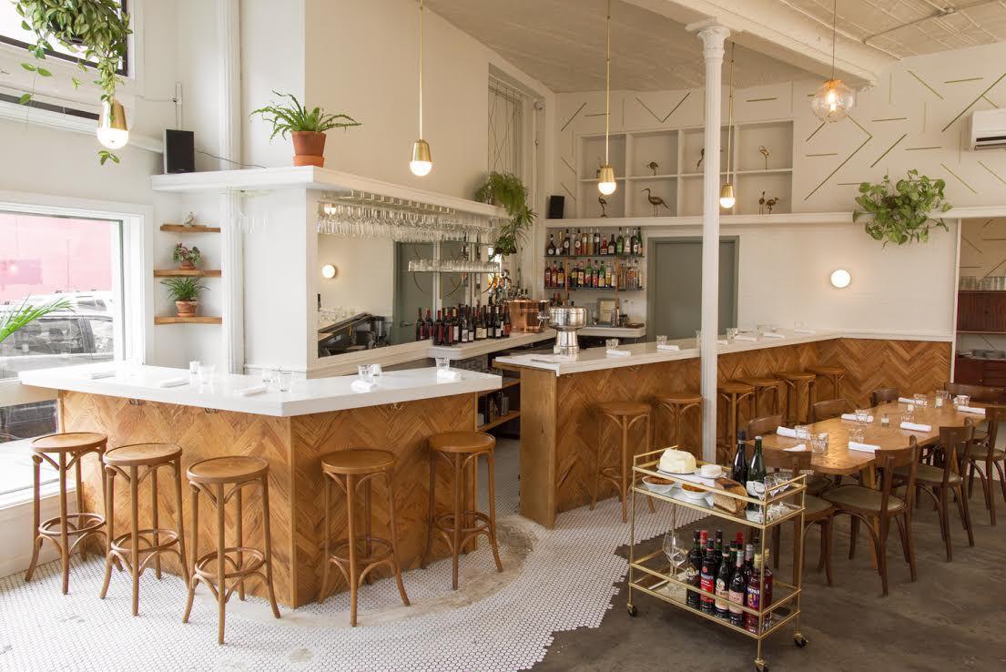 Das Innere eines Restaurants mit Marmortheken, Holztischen und -stühlen und Topfpflanzen, die von der Decke hängen