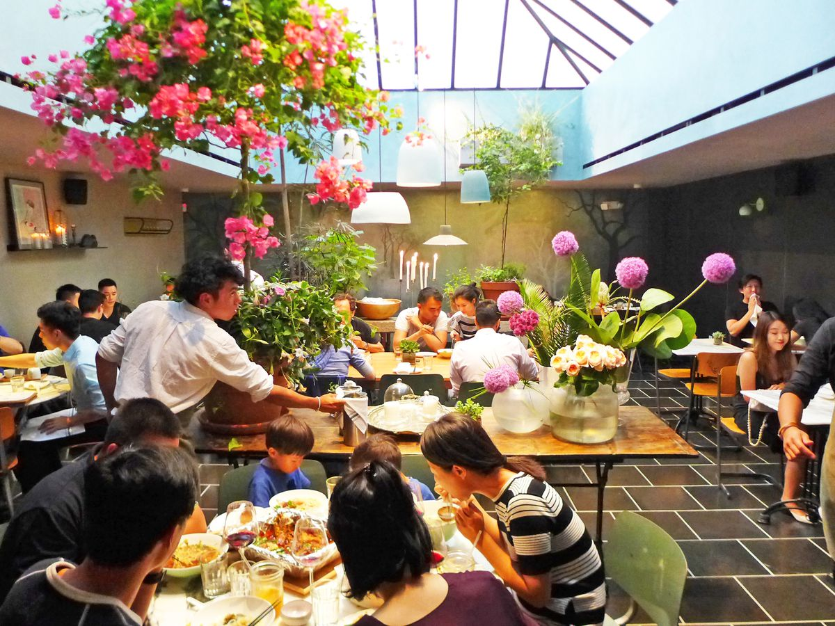Diners in a dining room with flowers and a skylight