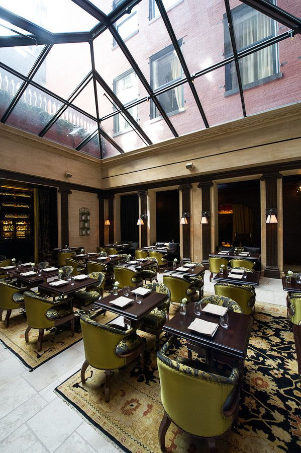The NoMad Restaurant's dining room has a high glass ceiling and dark brown tables