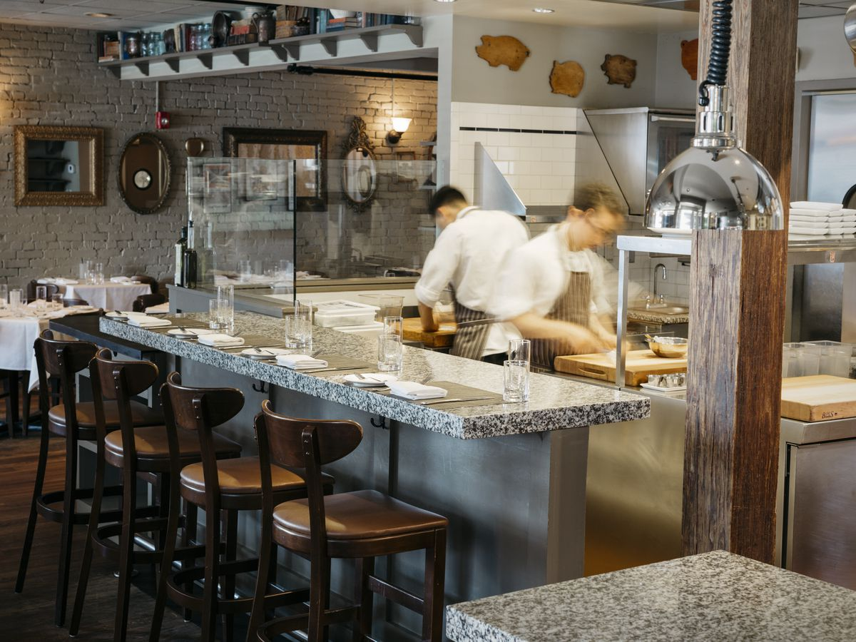 Two cooks work in the open kitchen at Craigie on Main in Cambridge, with a marble bar and high-top chairs in front of it and part of the dining room visible in the background.