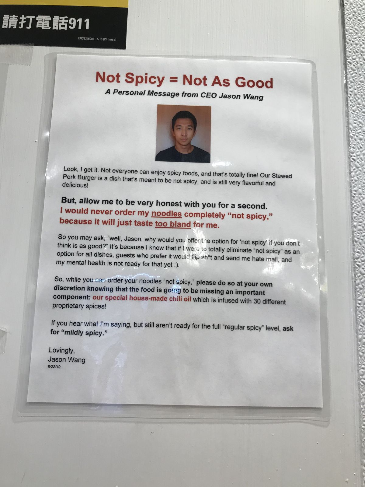"""A laminated letter denoting that """"Not Spicy = Not As Good,"""" with a photo of CEO Jason Wang"""
