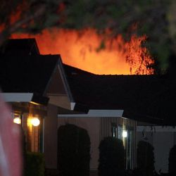This Thursday evening, April 12, 2012 photo shows the glow from a fire engulfing an apartment complex where authorities said a suspect was holed up following the shooting deaths of a deputy and a civilian in Modesto, Calif.