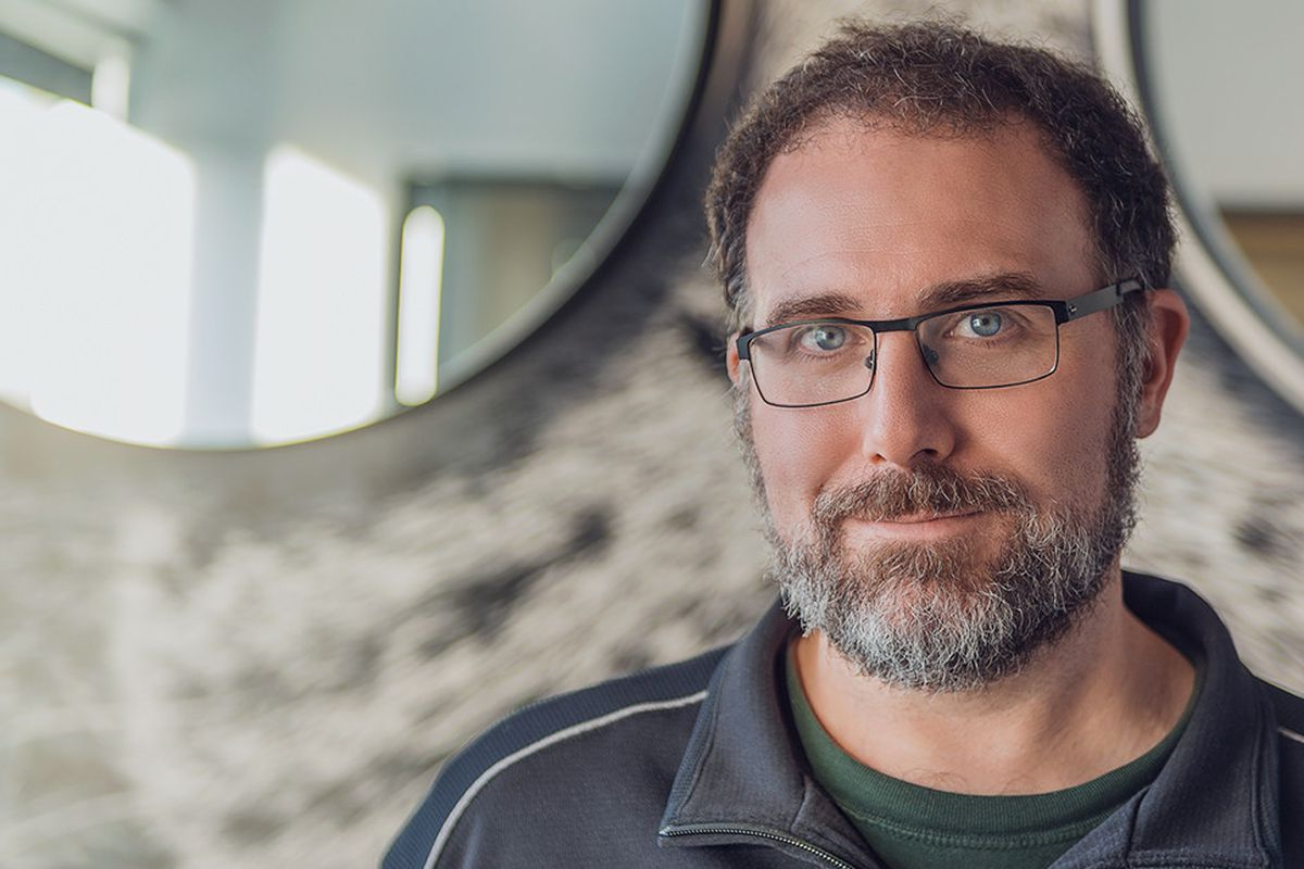 a publicity photo of Mike Laidlaw, who wears glasses and has a beard