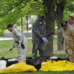 A kayaker in hazmat gear washes off so he can take off gear polluted by the oil spill in Liberty Park on Saturday.