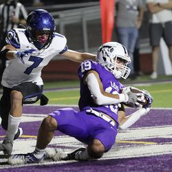 Lehi's Isaiah Tauai completes a pass for a touchdown in front of Pleasant Grove's Kolton Bayles during a football game at Lehi High School in Lehi on Friday, Sept. 11, 2020. Pleasant Grove won 35-29 in overtime.