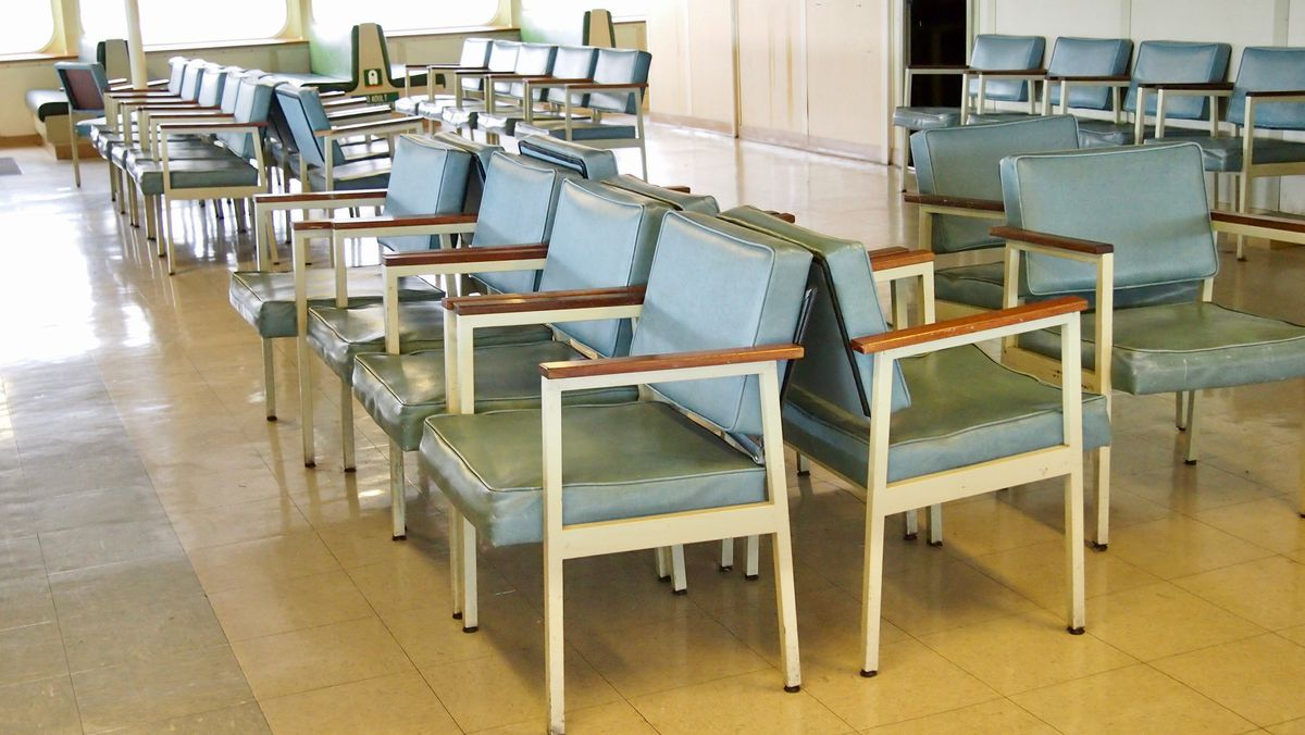 Rows of light green chairs with metal frames and wood grain arms.