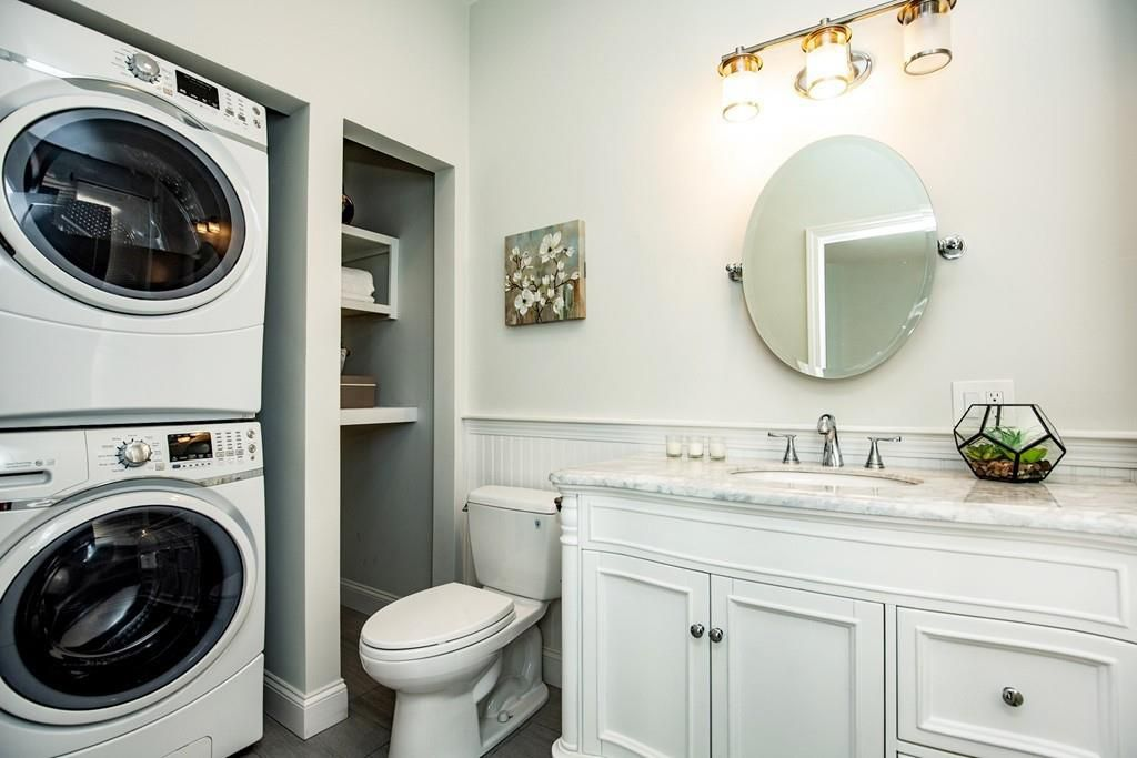 A bathroom with a vanity and a toilet perpendicular to a stacked washer-dryer.