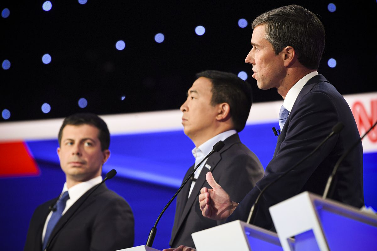 Democratic presidential hopefuls Mayor Pete Buttigieg, entrepreneur Andrew Yang, and former Representative Beto O'Rourke standing behind podiums at the fourth Democratic primary debate.
