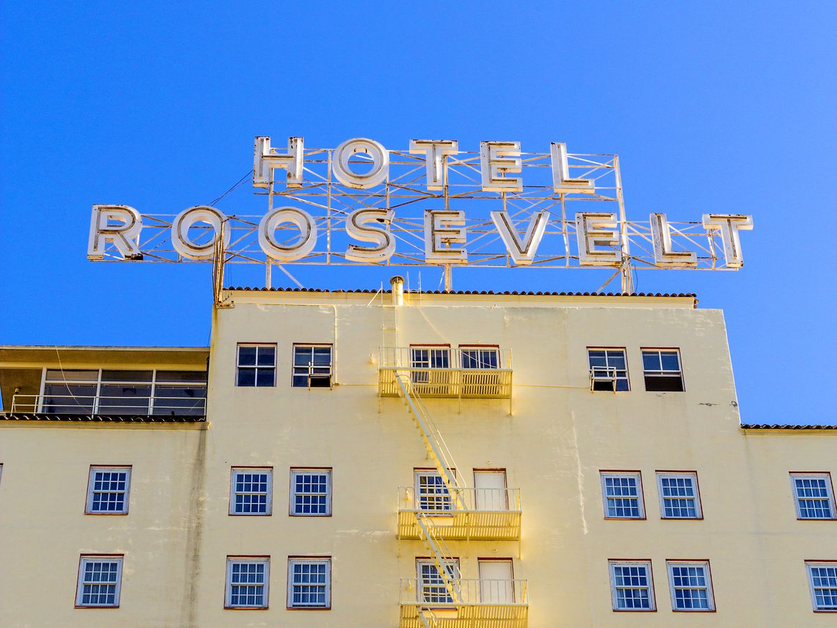 The exterior of the Hollywood Roosevelt in Los Angeles, California. The facade is tan and there are yellow fire escapes.