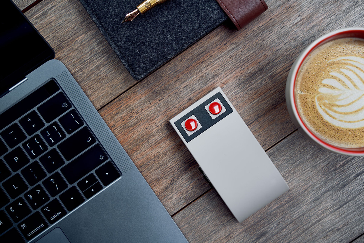 Product shot of the top of 8BitDo's NES-inspired wireless mouse on a wooden desk, with a laptop computer and latte in frame.