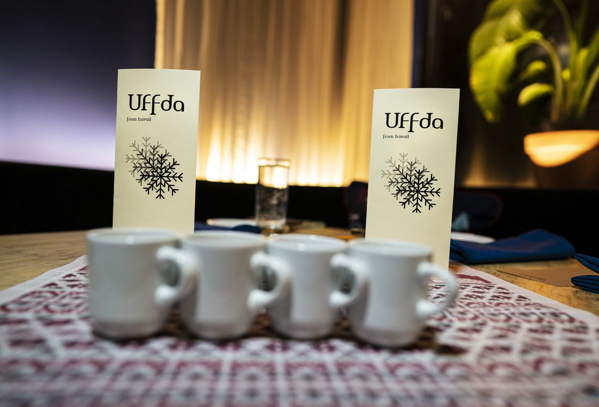 Coffee cups lined up on a table in front of two menus for Uffda