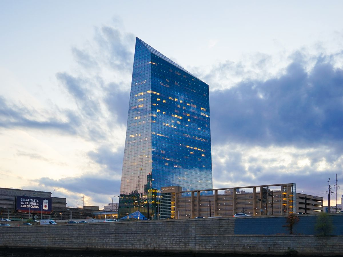 The exterior of Cira Centre in Philadelphia. The facade is glass and the roof is sloped.