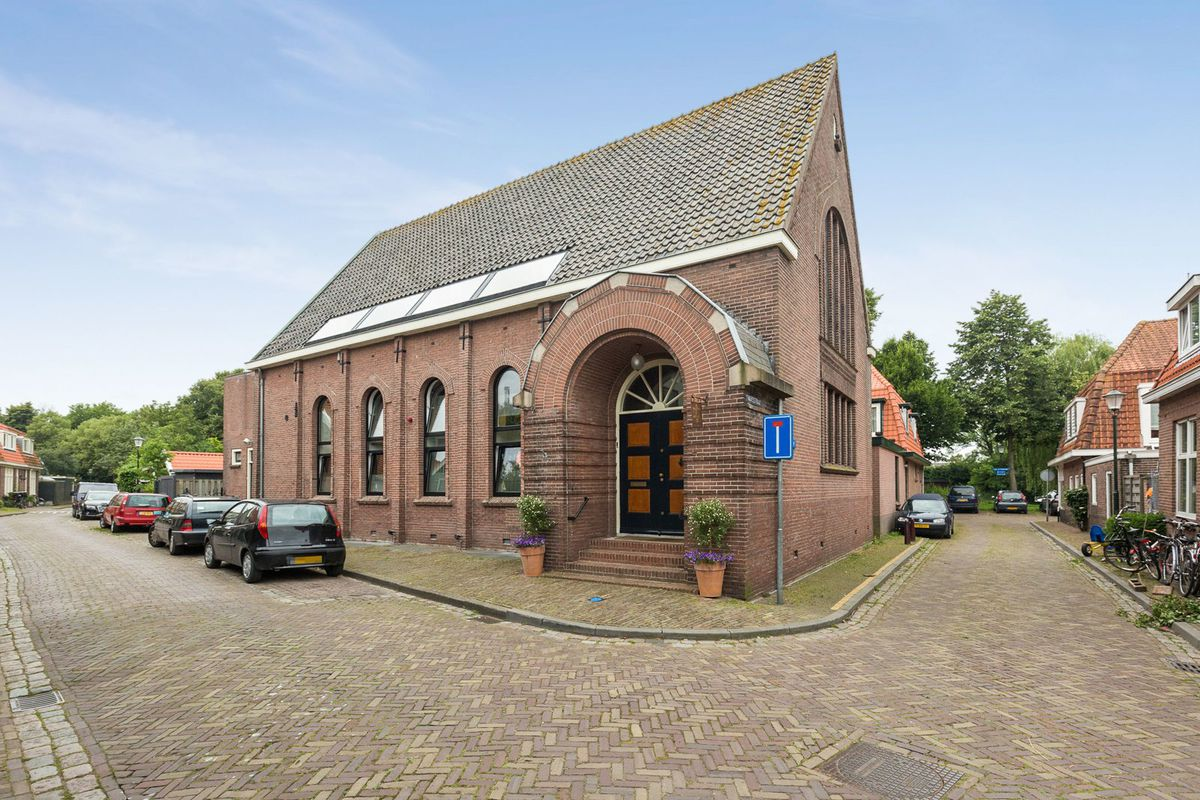 Brick church with high-pitched roof in small town setting.
