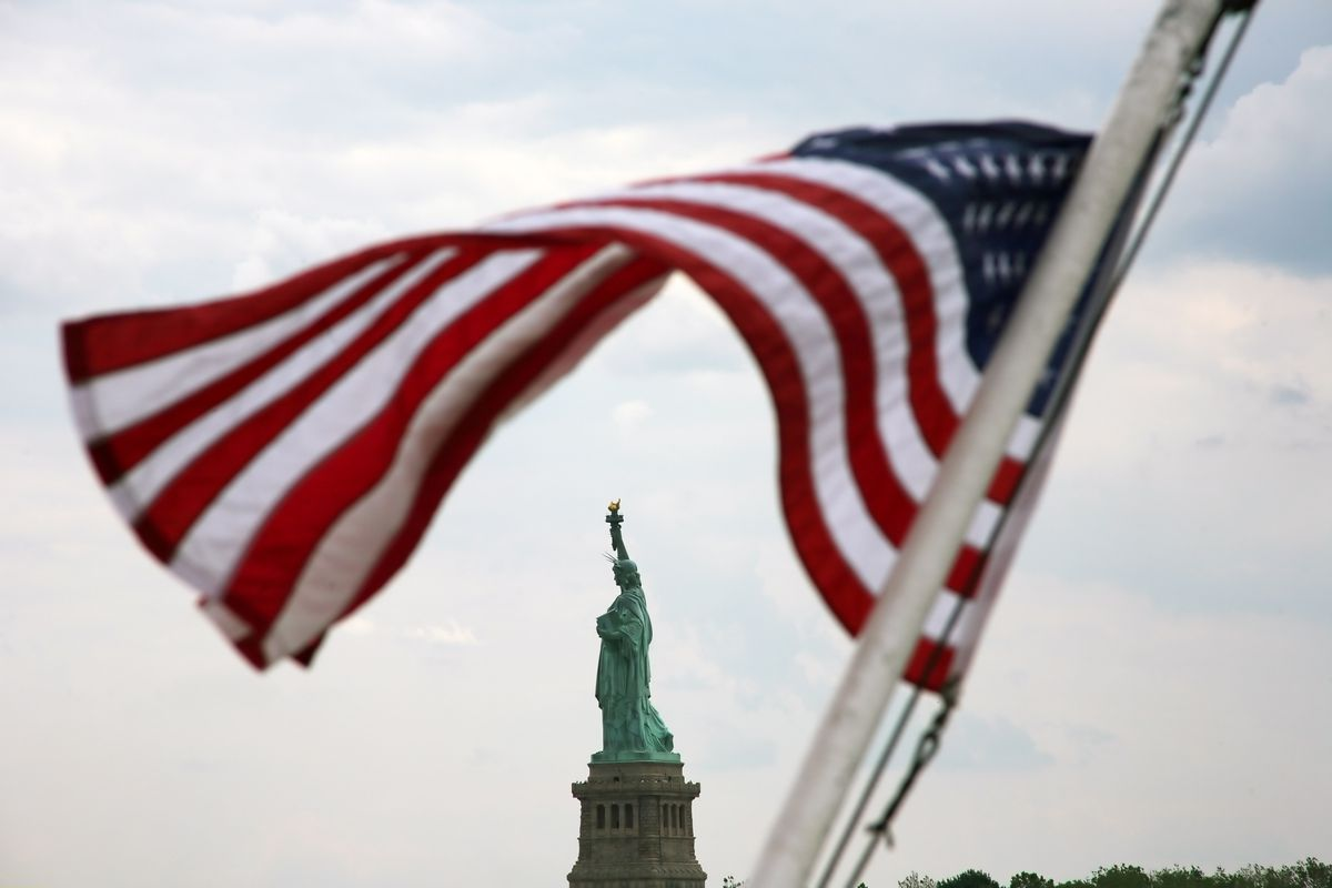 USA - New York City: The Statue of Liberty with the american national flag.